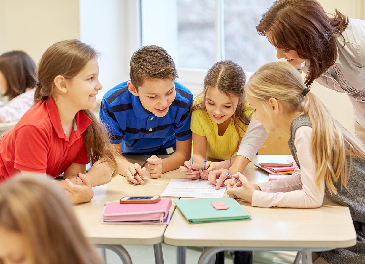 Foto de quatro alunos debruçados sobre uma mesa em sala de aula. São três meninas e um menino. Entre eles, há uma professora orientando uma tarefa e apontando sobre algo escrito no caderno de um dos alunos dolgachov – iStock