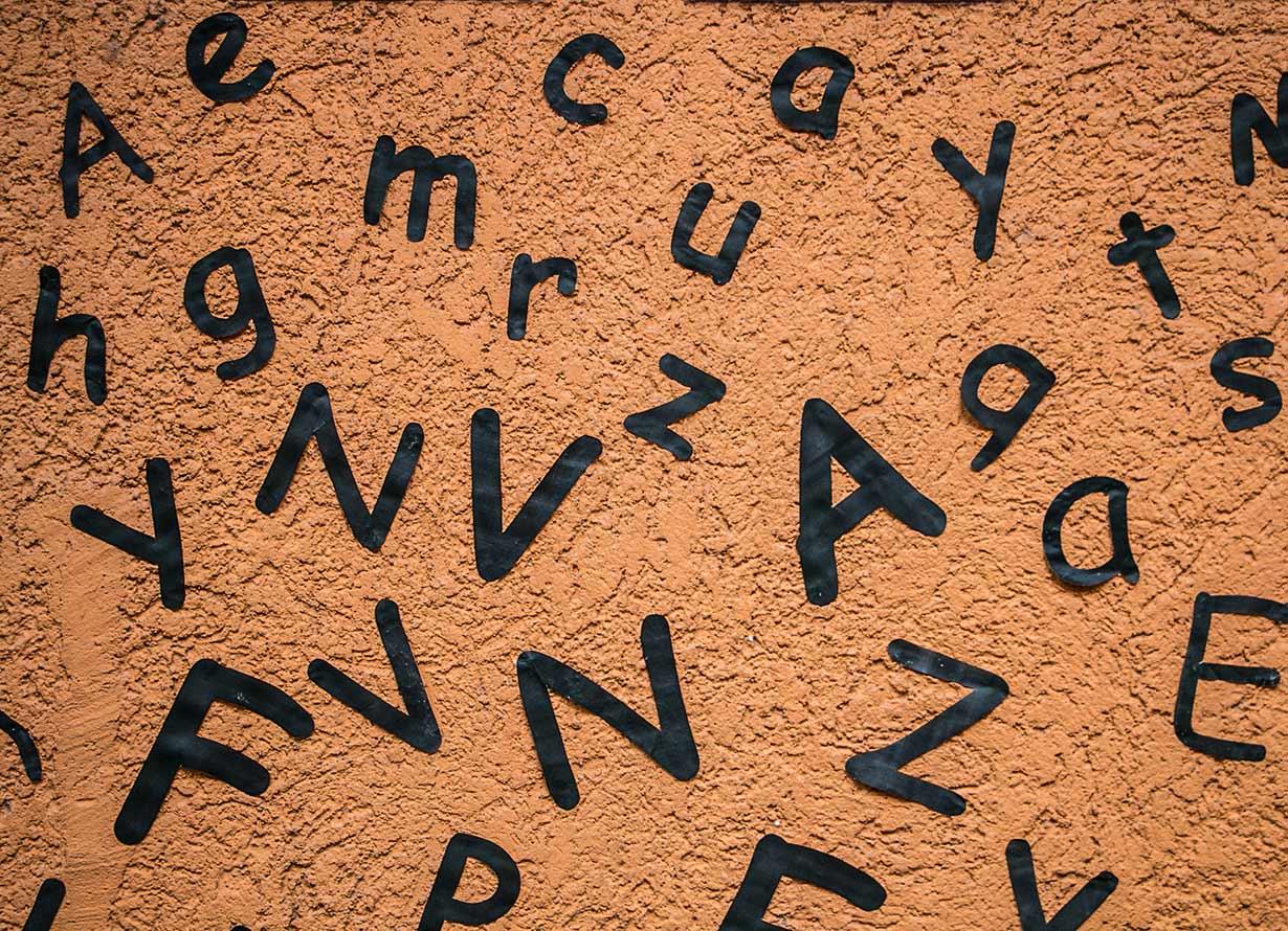 Arte em fundo marrom com diversas letras da cor preta espalhadas e em diferentes tamanhos. DanielleSalmoria – iStock