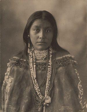 Foto em estilo sépia de uma mulher indígena. Ela está com feições tristes