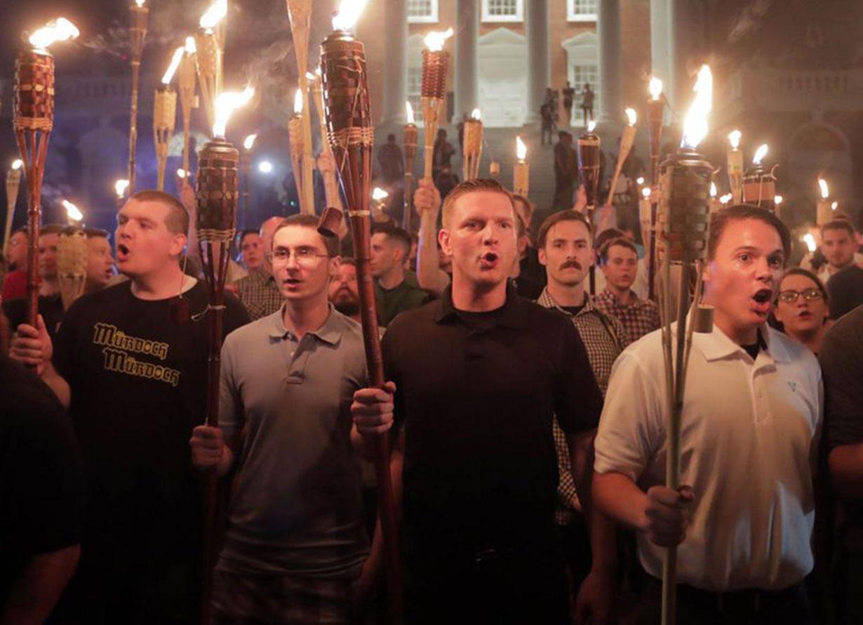 Foto de um grupo de homens segurando tochas durante um protesto.