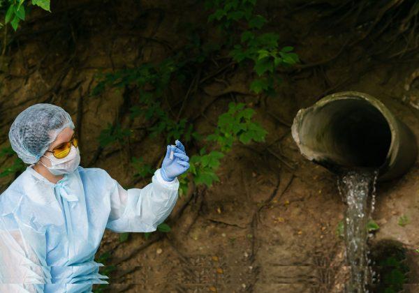 Foto de uma pessoa com roupas de segurança fazendo coleta de água para análise