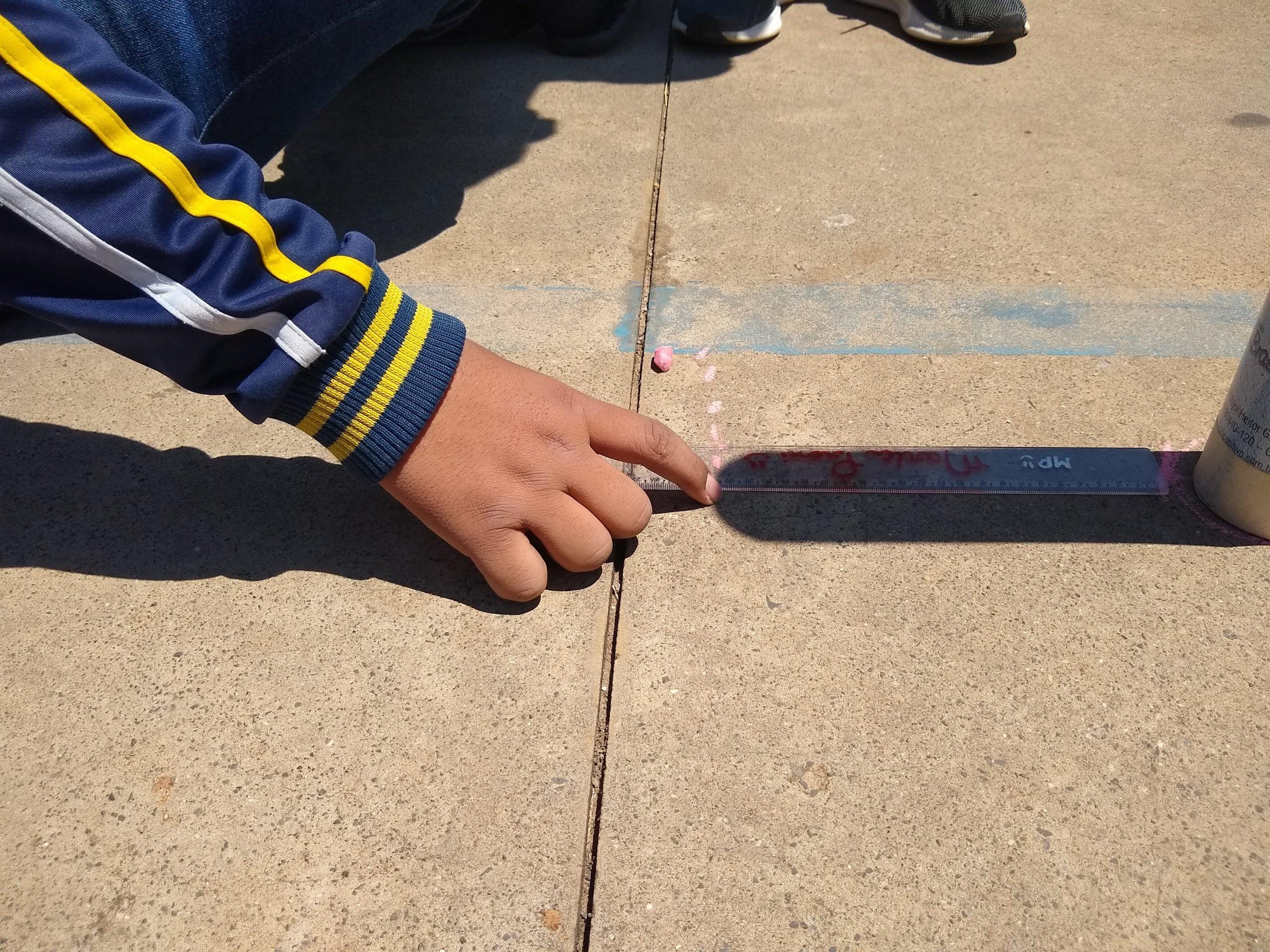 Aluno determina a sombra de uma haste vertical com o giz. As demais marcas mostram o movimento da sombra ao longo do tempo.