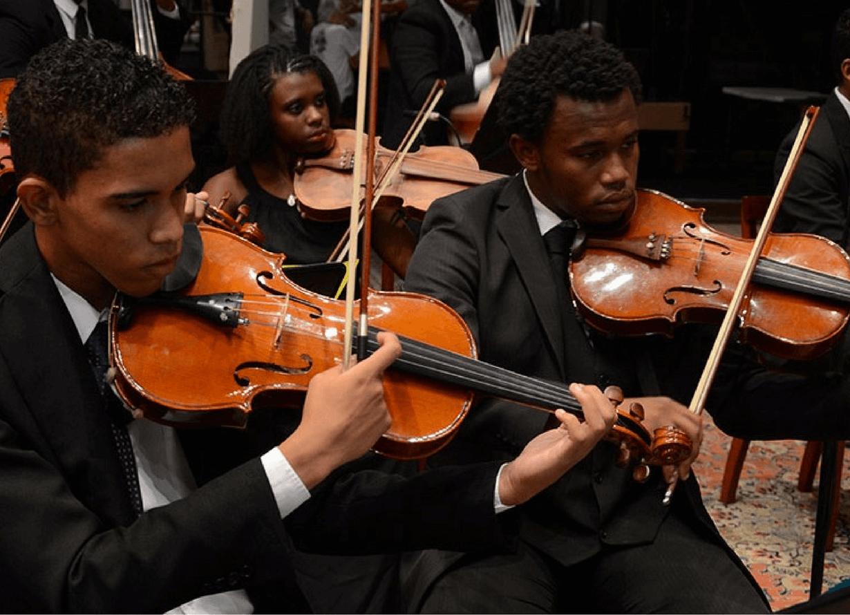 Foto de dois jovens de terno, sentados, tocando violino.