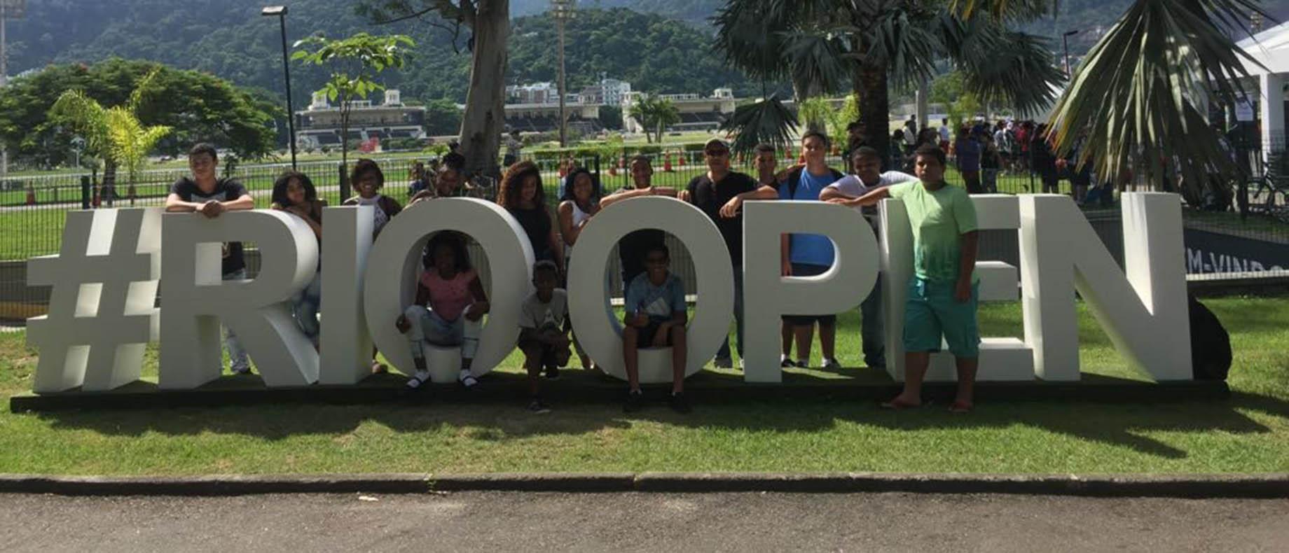 Foto de diversos jovens posando para uma foto juntos ao letreiro do Rio Open 2018 no jockey clube do Rio de Janeiro