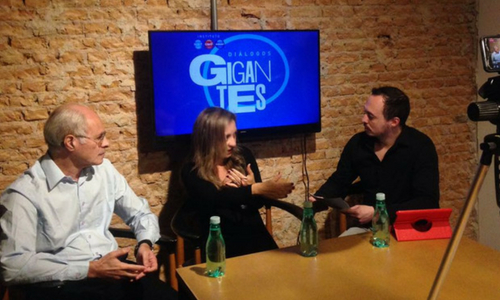 Foto de três pessoas durante um debate. Ao fundo, há uma tela com o título Diálogos Gigantes
