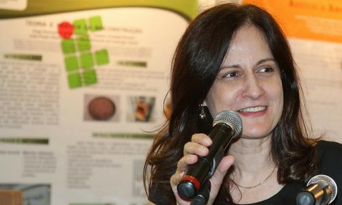 Foto de uma mulher sorrindo enquanto fala ao microfone