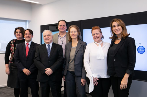 Foto de sete pessoas, sendo três homens e sete mulheres, lado a lado e sorrindo, em uma sala de escritório. Ao fundo, há uma tela com o logo do Instituto NET Claro Embratel.