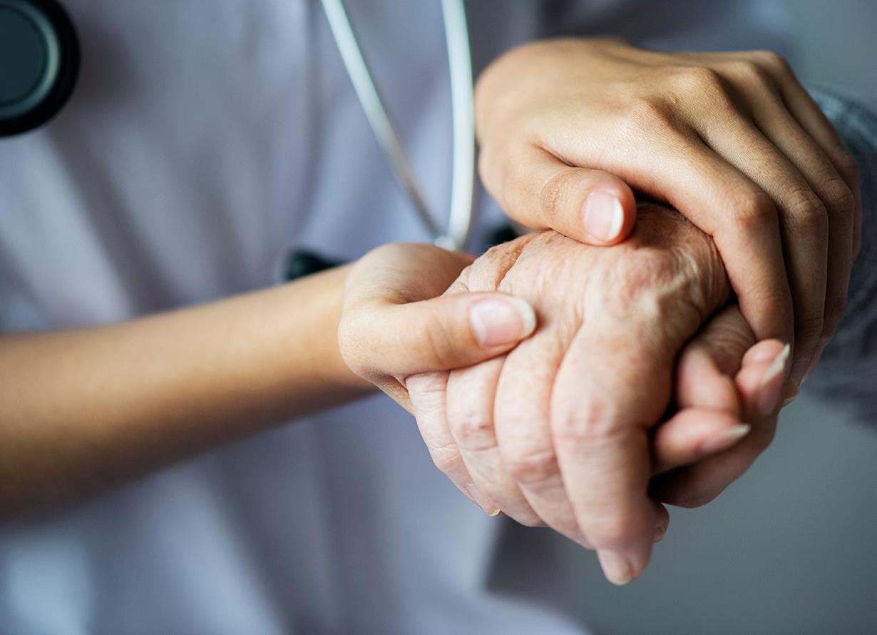 Foto das mãos de uma pessoa de jaleco e estetoscópio segurando a mão de uma pessoa idosa
