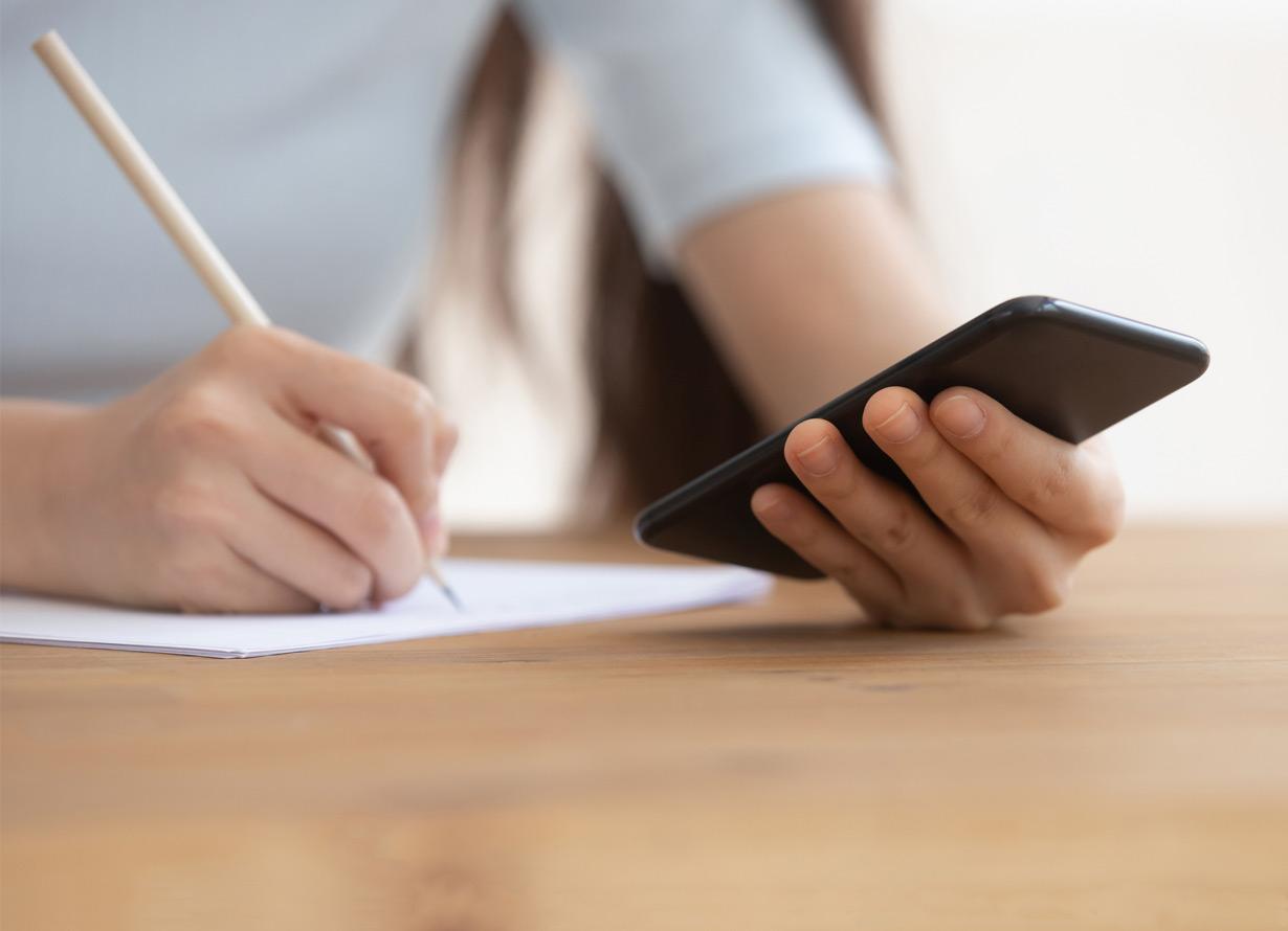 Foto em detalhe do dorso de uma mulher de frente sentada em uma cadeira. Ela escreve um papel que está sobre uma mesa e segura um celular