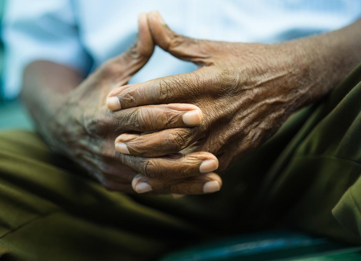Foto das mãos de um homem negro e idoso. Ele está com os dedos entrelaçados