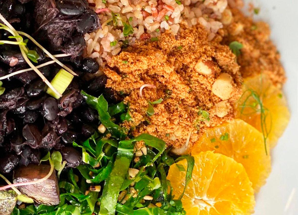 Foto em detalhe de prato com feijoada vegana, com feijão preto, arroz, couve, farofa e laranjas
