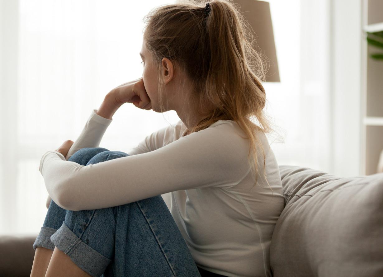 Foto de uma garota sentada no sofá olhando para o lado, ela está abraçando as pernas e com a mão no queixo