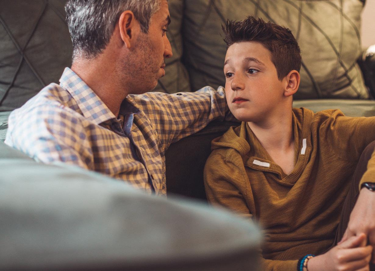Foto em detalhe de homem com o braço nos ombros de um garoto. Eles se olham e estão sentados no chão apoiados em um sofá