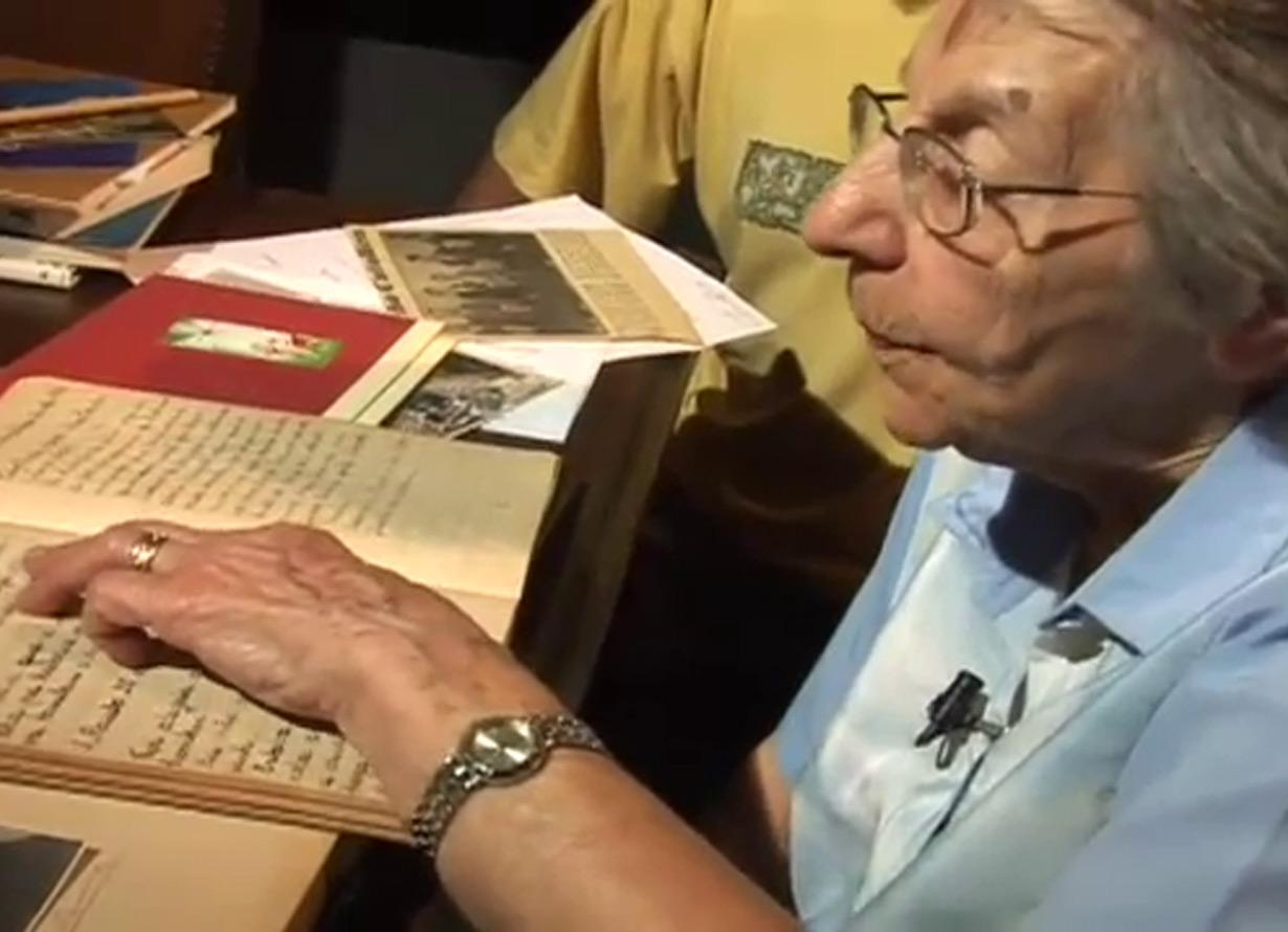 Foto de uma idosa de perfil. Ela passa o dedo em um diário antigo com as páginas por textos