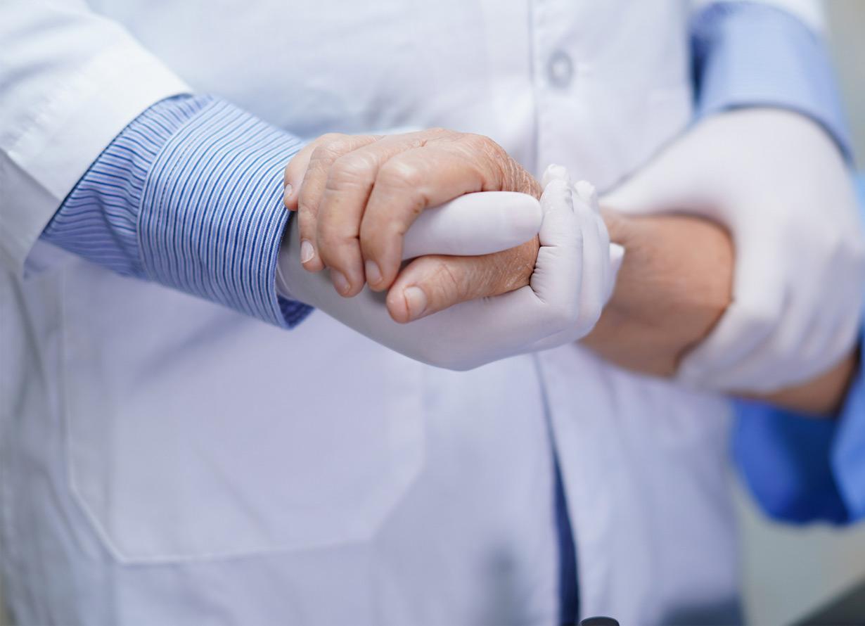 Foto em detalhe de mãos com luvas segurando, de forma cuidadosa e carinhosa, os braços de uma pessoa idosa