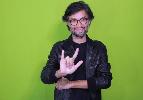 Foto de um homem, de cabelos castanhos, ele usa óculos de grau e uma jaqueta de couro preta. Com a mão direita, gesticula o sinal de amor em Libras