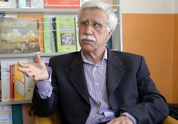 Foto de José Pacheco sentado, ele usa óculos e gesticula com a mão esquerda. Ao fundo há uma estante com alguns livros.