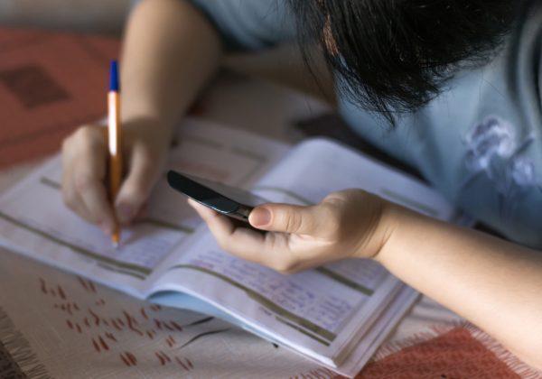 Foto, aproximada, de uma pessoa debruçada sobre a mesa, contendo um caderno aberto. Com uma das mães ela segura um celular e com a outra uma caneta.