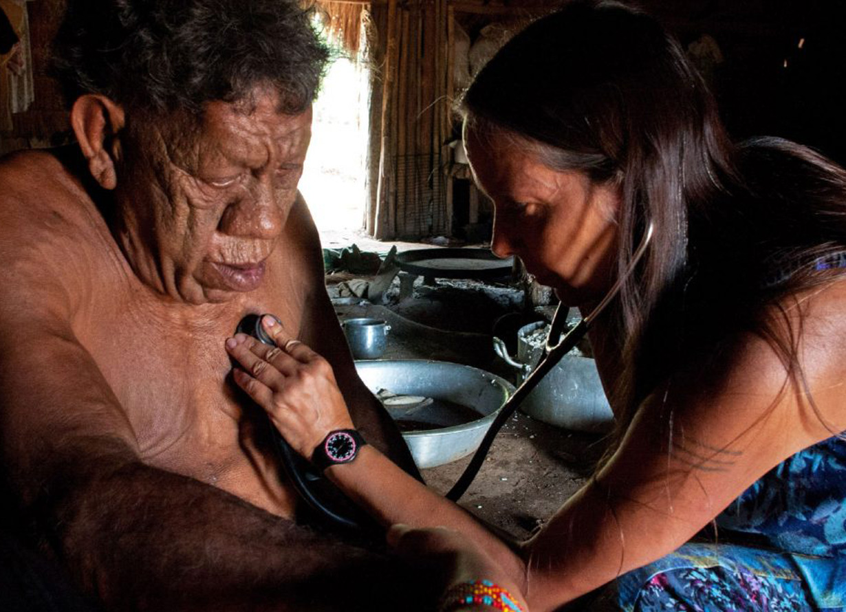 Foto de uma mulher indígena auscultando o coração de um senhor indígena com um estetoscópio
