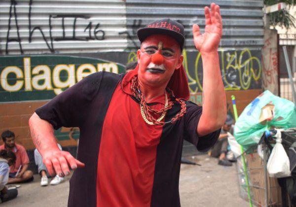 Foto de um homem, em situação de rua, com o rosto pintado de vermelho. Ele usa um nariz de palhaço, boné e camiseta nas cores vermelho e preto.