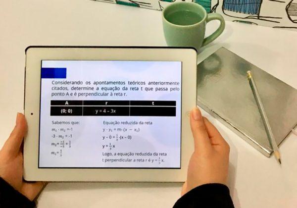 Foto de um par de mãos segurando um tablet, na tela deste há uma questão matemática. Ao fundo, sobre uma mesa, há uma caneca, caderno e lápis.