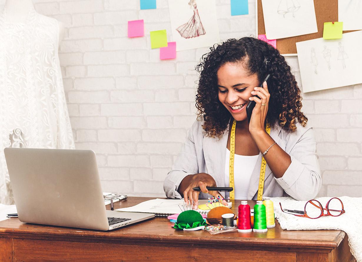Foto de uma mulher negra falando ao celular. Ela está sentada atrás de uma mesa com um computador e diversos papéis e artigos de costura.