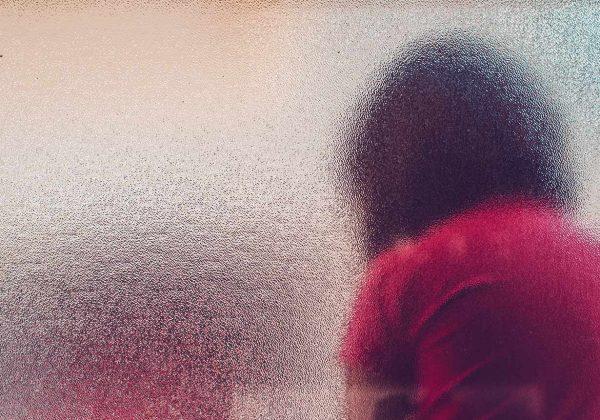 Foto de uma criança de costas, sobre ela há uma textura de vidro, que embaça a imagem.