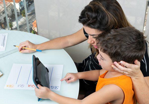Foto de uma mulher, sentada de frente a uma mesa. Ela está ao lado de um menino. Ele segura um tablet e aponta para a tela.