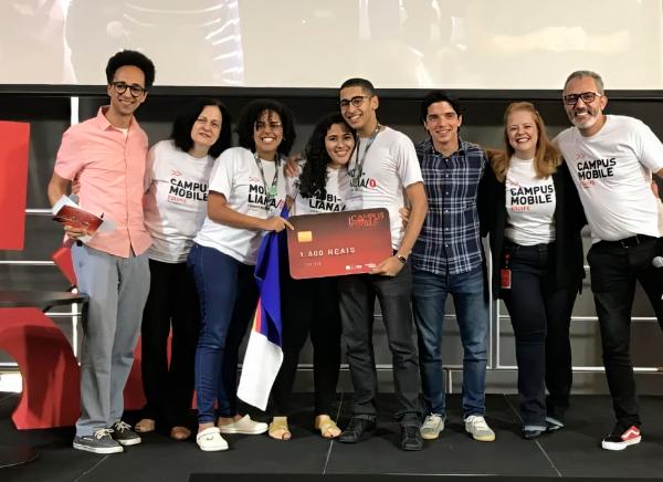 Foto de um grupo diverso de pessoas lado a lado sobre um palco. Elas se abraçam e sorriem