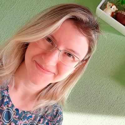 Foto em formato selfie de uma mulher loira. Ela usa óculos de grau e sorri