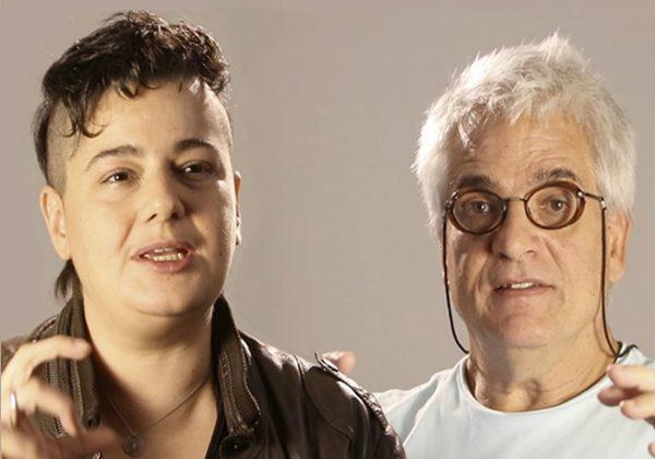 Foto, de fundo cinza, contendo à esquerda uma mulher de cabelos curtos em cima e raspados nas laterais; e à direita um homem de cabelos grisalhos e óculos. Ambos gesticulam as mãos.
