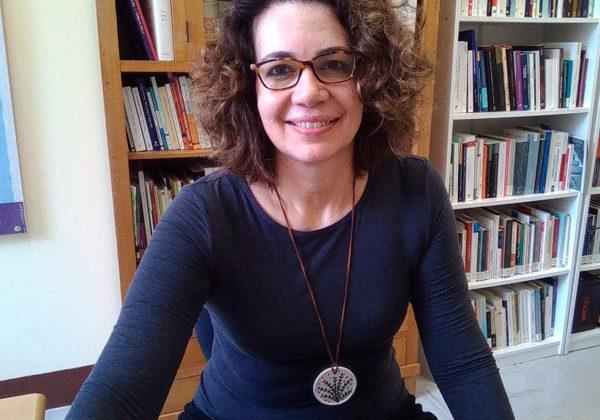 Foto, da cintura para cima de uma mulher branca, de cabelos castalhos, curtos e encaracolados. Ela usa óculos de grau. Ao fundo há uma estante cheia de livros.