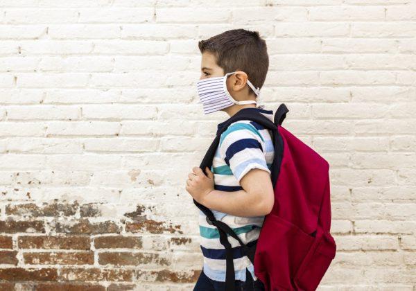 Foto de um menino caminhando, ele usa máscara de proteção e tem uma mochila nas costas. Ao fundo há um muro de tijolos brancos, com o canto inferior descascado.