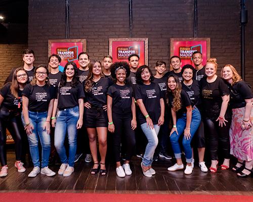 foto de um grupo de jovens em pé posando para uma fotografia. Eles estão sorrindo e vestem camisetas pretas