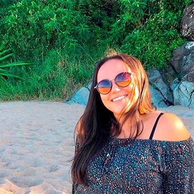 Foto de uma mulher de cabelos castanhos e lisos sorrindo na praia. Atrás dela, há pedras e árvores.