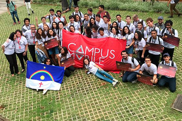 Foto tirada de cima de um grupo diverso de pessoasem um local gramado. Eles sorriem e alguns seguram uma faixa vermelha do Campus Mobile e réplicas de cartões de crédito em tamanho grande nas mãos
