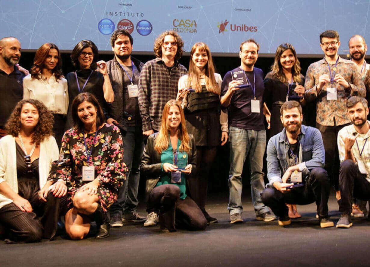 Foto de um grupo diverso de pessoas posando na frente de um palco. Atrás deles, há um telão com o logo do seminário NETLABTV