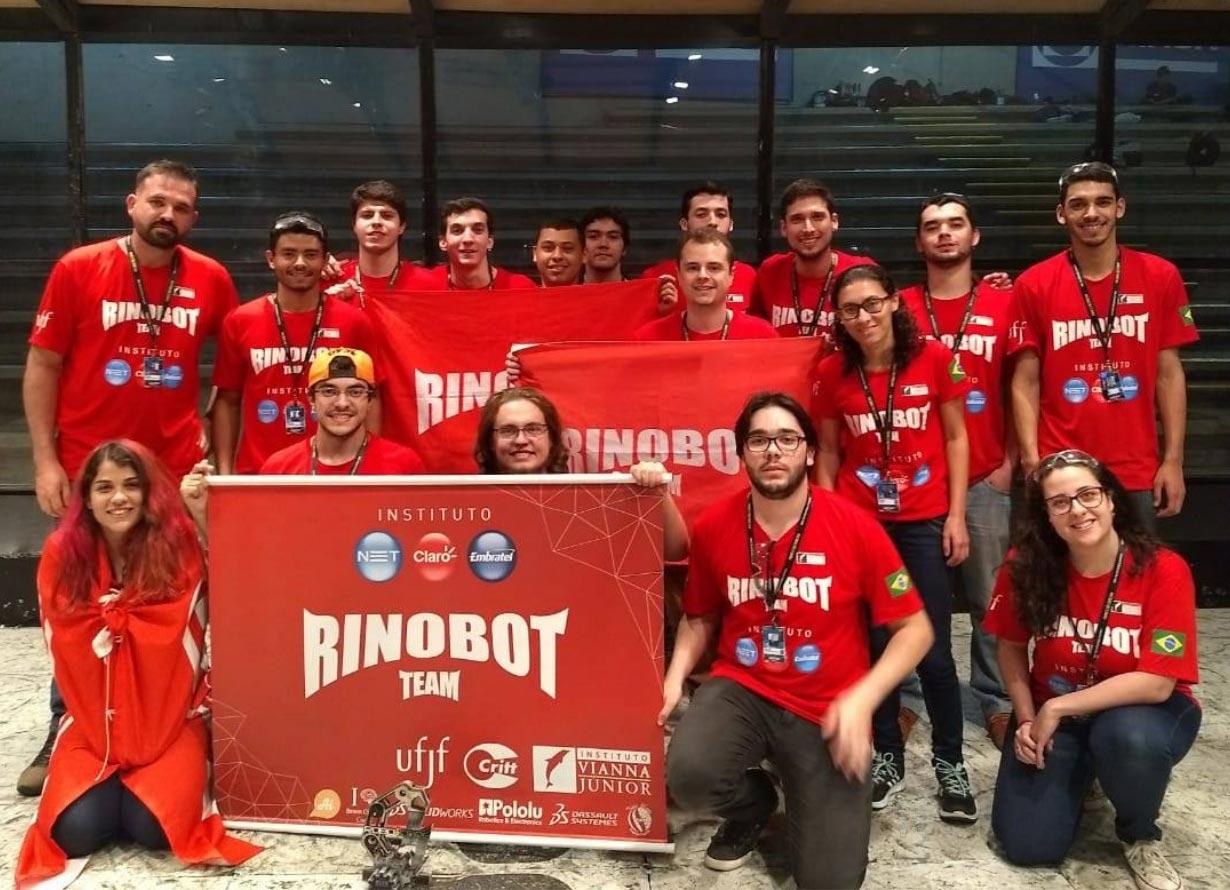 """Foto de um grupo diverso de jovens com camisetas e bandeiras vermelhas com a escrita """"Rinobot"""""""