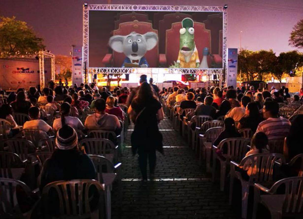 Foto de uma plateia ao ar livre assistindo um filme.